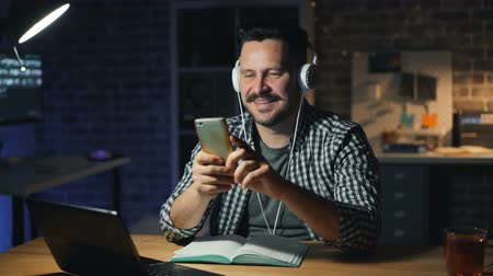 wearing earphones : Attractive guy is using smartphone touching screen smiling and listening to music through headphones in office at night. Gadgets and lifestyle concept.