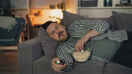 pipoca : Portrait of attractive man watching film on TV at night at home in cozy apartment lying on sofa and eating popcorn looking at camera. Youth and house concept. Stock Footage