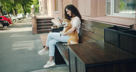 shiba inu : Smiling girl is using smartphone touching screen and hugging adorable shiba inu dog outdoors in the street cafe sitting on bench. People, devices and pets concept.
