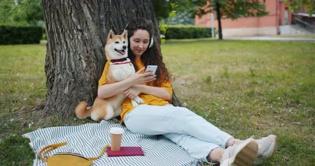 shiba inu : Modern girl is listening to music with headphones and using smartphone relaxing in city park with pet dog, stroking and caressing the animal. People and leisure concept.