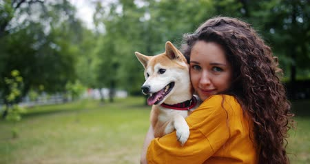 shiba inu : Portrait of happy young woman holding beautiful puppy in park in summer smiling looking at camera. Modern lifestyle, domestic animals and love concept.