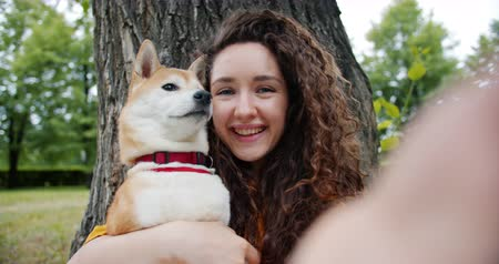 shiba inu : Portrait of happy young girl taking selfie with adorable dog in park hugging lovely pet holding camera smiling enjoying friendship with puppy. Youth and lifestyle concept. Stock Footage