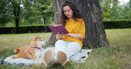 shiba inu : Slow motion of attractive young woman reading book in park on summer day sitting on lawn with shiba inu dog. Hobby, lifestyle and youth culture concept. Stock Footage