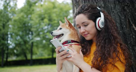 shiba inu : Smiling female student is enjoying music in headphones and using smartphone sitting on grass in park with beautiful dog. People, pets and nature concept.