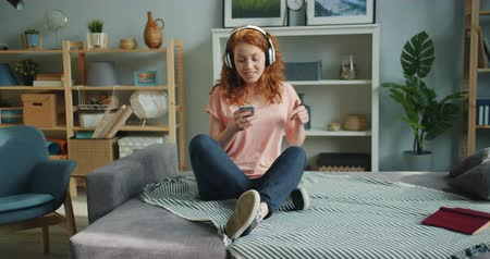 хорошее настроение : Slow motion of cute girl listening to music in headphones dancing and using smartphone at home sitting on couch in bedroom. People, fun and youth concept.
