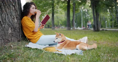 shiba inu : Relaxed girl is drinking coffee and reading book in park sitting on lawn with shiba inu dog enjoying leisure time. Modern lifestyle, people and pets concept. Stock Footage