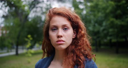 szeplők : Slow motion portrait of pretty lady with red hair wearing casual clothing standing in the park with serious face and looking at camera. Nature and youth concept.