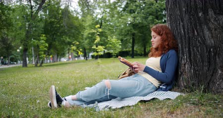 vöröshajú : Beautiful young woman is reading book sitting on blanket under tree in park and smiling enjoying summertime and literature. People and lifestyle concept.