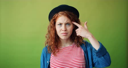 anlamı : Portrait of teenager twisting finger at head making fool sign looking at camera spreading hands standing alone on green background. People and attitude concept. Stok Video