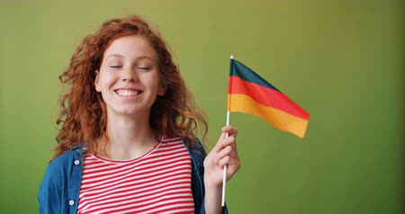 гордый : Beautiful redhead girl hipster is holding German flag smiling standing on green background with curly hair flying in the wind. People and nationality concept. Стоковые видеозаписи