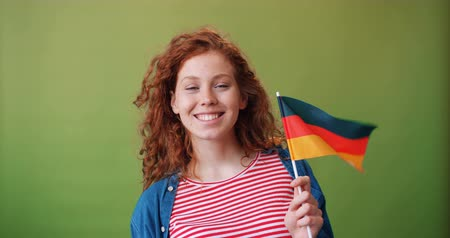 büszke : Charming German teenage girl holding national flag of Germany smiling standing on green background enjoying patriotic feelings. Youth and countries concept. Stock mozgókép