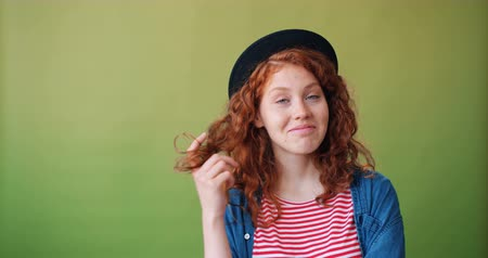 coqueteo : Portrait of cute teenage girl winding hair around finger smiling flirting looking at camera standing on green background. Beautiful women and flirt concept. Archivo de Video