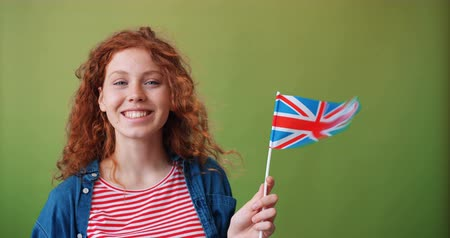 nationality : Cute red-haired girl is holding British flag on green background smiling looking at camera. Great Britain, worls travelling, nationality and youth concept. Stock Footage