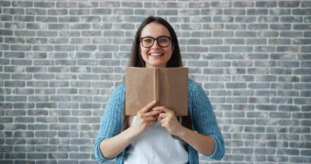művelt : Portrait of happy girl in glasses reading book hiding face then smiling standing on brick wall background. Youth culture, education and lifestyle concept.