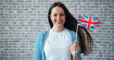 гражданство : Portrait of pretty young woman with British flag standing alone on brick wall background smiling looking at camera with happy face. Tourism and world concept.