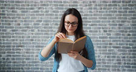 művelt : Serious girl in glasses is reading interesting book turning page standing alone on brick wall background. Modern lifestyle, education and youth concept.