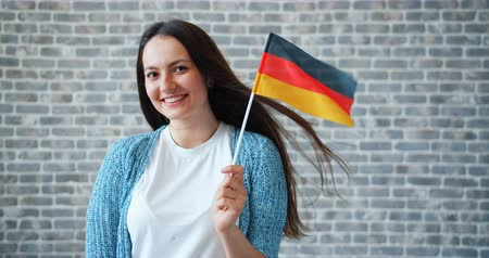 гражданство : Portrait of attractive young woman holding national German flag standing on brick wall background and smiling. Patriotism, youth and world tourism concept.