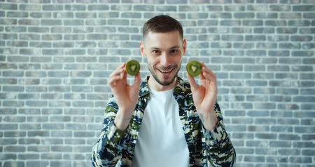 キウイ : Portrait of handsome young man with kiwi fruit on eyes smiling standing on brick wall background having fun. Healthy food, modern lifestyle anf youth concept.