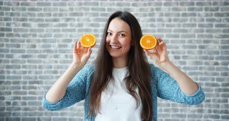laranjas : Portrait of pretty young lady holding oranges and smiling on brick wall background offering fresh fruit and healthy lifestyle. People and health concept.
