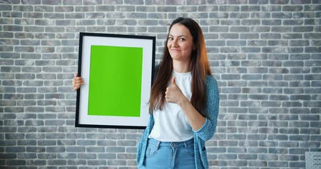 képek : Portrait of girl pointing at green screen chroma key picture showing thumbs-up smiling standing on brick wall background holding frame. People and emotions concept.