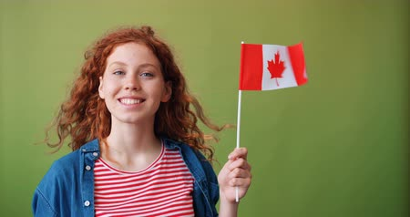 kanada : Pretty girl with happy face is holding national flag of Canada standing on green background smiling looking at camera. People, countries and travelling concept.
