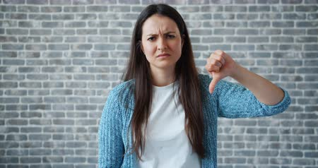 失望 : Portrait of unhappy girl with long black hair showing thumbs-down on brick wall background. Dislike gesture, disappointed people and attitude concept. 動画素材