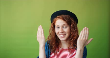 幼稚な : Portrait of cheerful girl in trendy hat playing hide-and-seek then smiling on green background. Joyful millennials, emotions and happy young people concept.