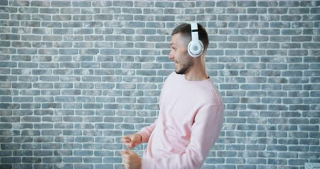 feliz : Portrait of bearded young man listening to music in headphones and dancing on brick wall background. Modern gadgets, lifestyle and happy youth concept. Stock Footage