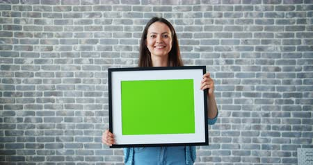 フレーム : Portrait of beautiful girl holding green chroma key mockup picture and smiling standing on brick wall background. People, green screen and emotions concept.