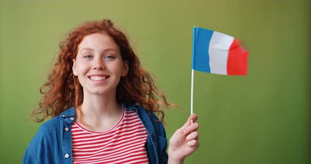 büszke : Female French patriot beautiful teenage girl holding flag of France smiling looking at camera standing alone on green background. Patriotism and young people concept.