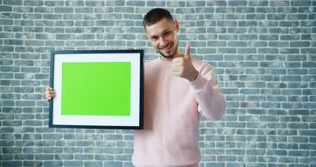 Картинки : Portrait of handsome man holding chroma key picture frame and showing thumbs-up expressing high evaluation on brick wall background. People and like concept. Стоковые видеозаписи
