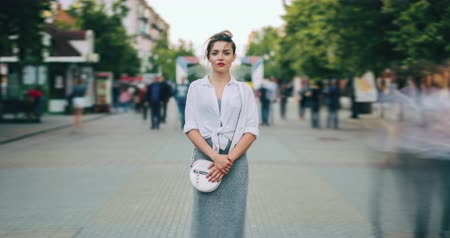 opvallen : Zoom out of good-looking young lady standing alone on busy city street looking at camera while crowd of pedestrians in passing by. People and lifestyle concept. Stockvideo