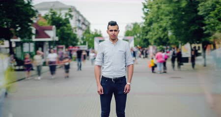 outsider : Zoom in time lapse portrait of Arabian student standing in street among flow of people looking at camera with serious face. Youth, modern life and summer concept.
