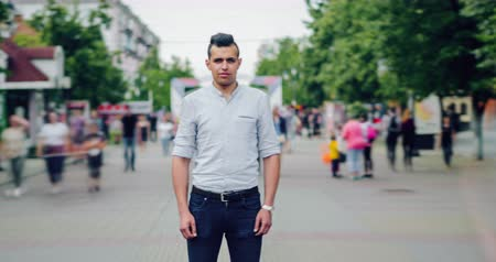 outsider : Time lapse of serious mixed race man standing alone in busy pedestrian street in city looking at camera while crowd of people is passing around. Youth and life concept.