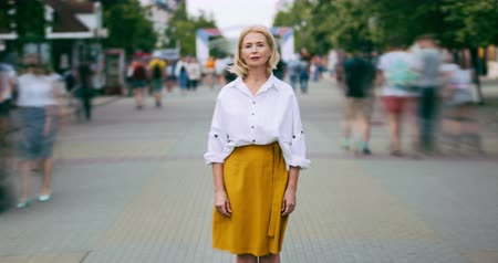 kifinomult : Zoom out time lapse of pretty mature woman looking at camera standing in street metropolis with serious face wearing elegant clothing while people are rushing around. Stock mozgókép