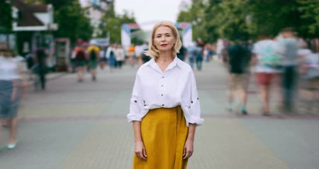 kifinomult : Time lapse portrait of beautiful mature lady with serious face in city street standing alone looking at camera. Summer town, people and modern life concept. Stock mozgókép