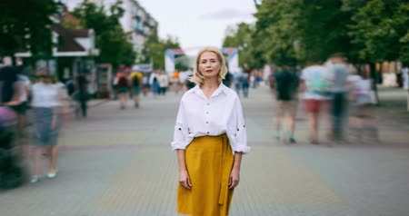 milestone : Zoom in time lapse of attractive mature blonde standing in city street on summer day looking at camera alone. Modern lifestyle, people and society concept.