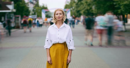 crowds of people : Time lapse portrait of good-looking mature woman in elegant clothing in street standing alone looking at camera with serious face. People, life and summer concept. Stock Footage