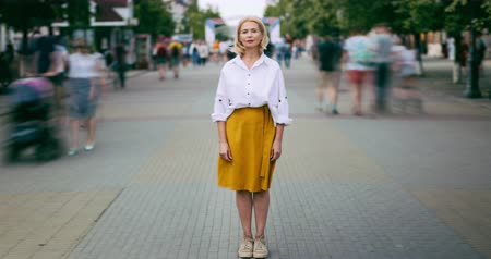 бросаясь : Time lapse of attractive mature woman standing in city in busy street looking at camera wearing casual clothes while crowds of people are rushing around.