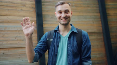 anız : Slow motion of friendly handsome guy waving hand smiling outdoors standing in the street alone greeting people looking at camera. Youth and hello concept. Stok Video