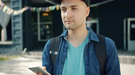 sırt çantasıyla : Portrait of attractive young man student using smartphone touching screen outdoors standing in city street alone. Devices, people and modern youth concept. Stok Video