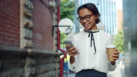 uscire : Smiling African American woman is using smartphone holding take out coffee walking outdoors in the street. People, devices and moden lifestyle concept.