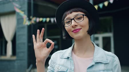 approving : Slow motion of pretty young lady showing OK gesture outside smiling looking at camera standing alone. Beautiful people, human emotions and city concept. Stock Footage