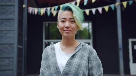 korhadt : Portrait of Asian punk with nose piercing and dyed hair smiling outdoors looking at camera with light smile. Stylish people, emotions and city concept.