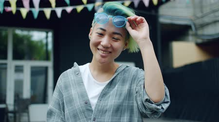 barvivo : Slow motion of joyful Asian hipster with blue dyed hair and nose piercing raising sunglasses smiling outdoors looking at camera standing in city street alone.