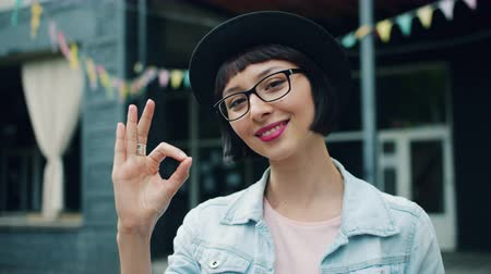 stare bene : Portrait of beautiful young woman showing OK hand gesture outdoors smiling looking at camera. Happiness, approval and modern happy millennials concept. Filmati Stock