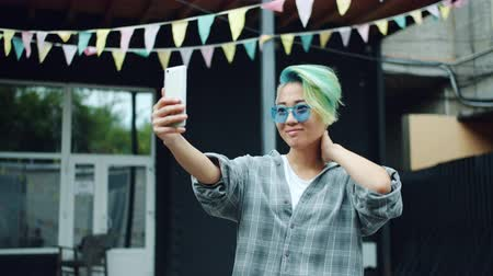 korhadt : Stylish Asian girl in sunglasses is taking selfie with smartphone camera outdoors posing touching dyed hair and smiling. Modern youth and photo concept.