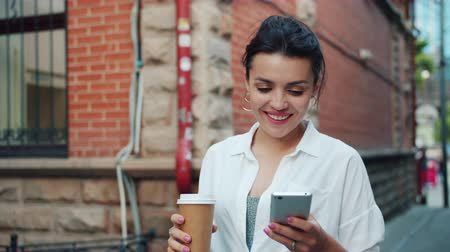 uscire : Slow motion of beautiful lady using smartphone holding to go coffee walking outdoors smiling in the street. People, devices and moden lifestyle concept. Filmati Stock