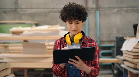 craftswoman : Female worker is busy with inventory in wood workshop using tablet walking looking around holding gadget. Business, modern technology and people concept. Stock Footage