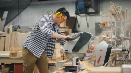 óculos de proteção : Woordworker man in protective glasses and headphones is working with electric saw busy sawing wood in workshop. Business, people and woodwork concept.